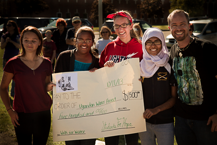 Students holding large check with fundraising total amount