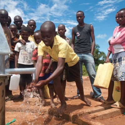 Boy fetching water at restored borehole well