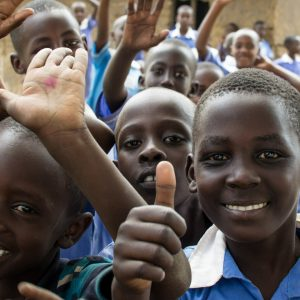 Happy ugandan children waving and giving thumbs up